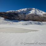 Laghetto ghiacciato e sullo sfondo Monte Pollino